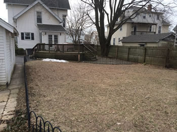 Before picture of a large backyard, void of grass, with a patio and a small fence.