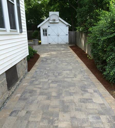 Paver driveway along side the house leading to the garage.