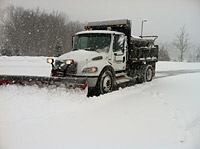 Entire scene covered in thick snow with large truck with a front snow plow making a large passageway.